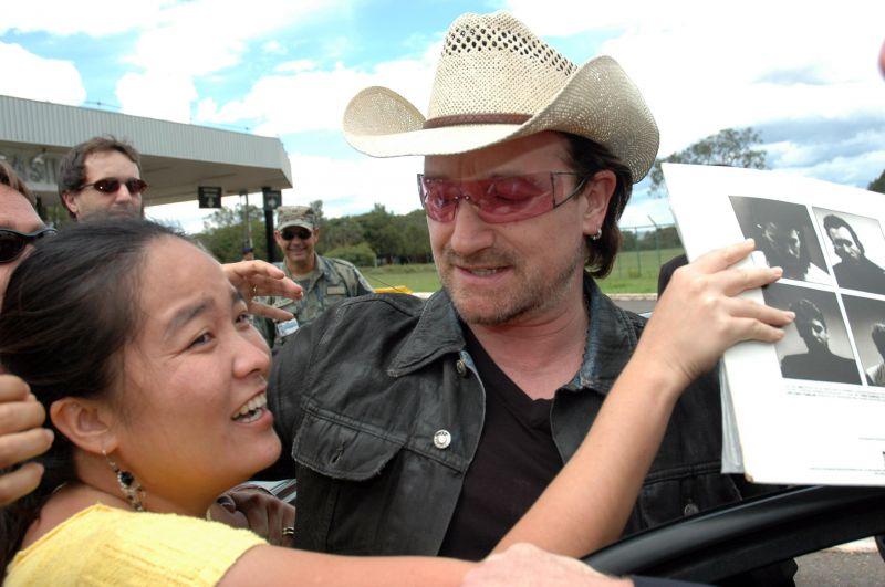 Bono, líder do U2, desce do carro para conversar com fãs, em frente à Base Aérea de Brasília. Foto de Breno Fortes (19/02/2006)