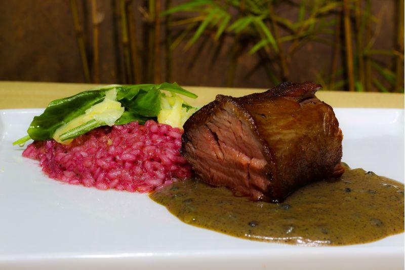 Crédito: Raphael Campos/Divulgação.Filé-mignon poivre sobre risoto de tomate seco, rúcula e beterraba com grana padano do restaurante Tropo.