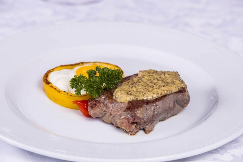Créditos: Rômulo Juracy/Divulgação. Filé ao molho Dijon com flor de pimenta e ovo do menu Ravenna do restaurante Dalí Camões.
