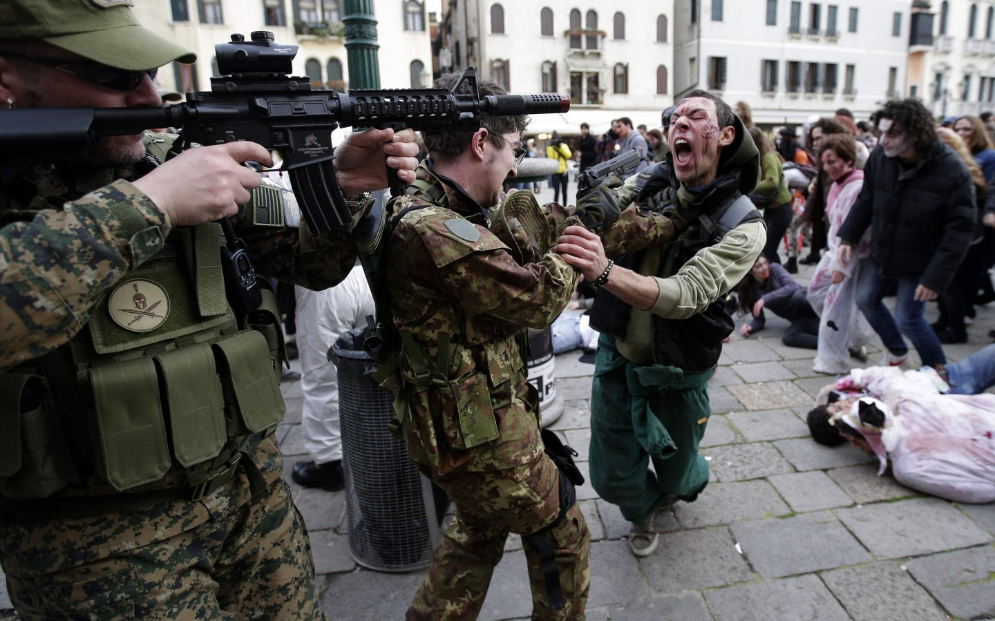 "Participants dressed as zombies and soldiers simulate a fight during a ""Zombie Walk"", part of the Venetian Carnival, in Venice February 15, 2014. REUTERS/Max Rossi (ITALY - Tags: SOCIETY TRAVEL) ORG XMIT: MXR10"