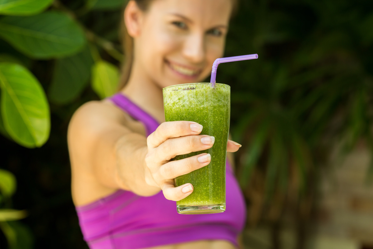 Athletic girl holding a green smoothie
