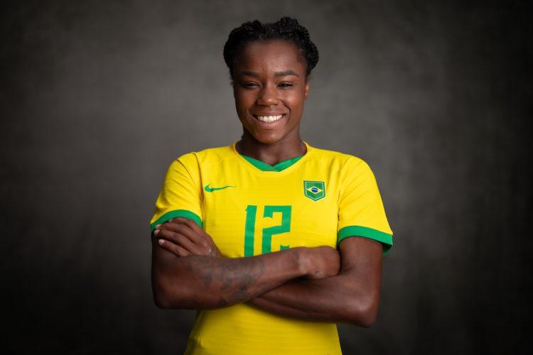 A atacante Ludmila está vestida com a camisa amarela da Seleção Brasileira e aparece sorrindo, com os braços cruzados