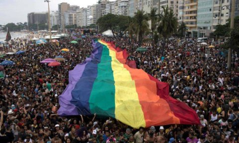 People-hold-a-huge-rainbow-flag-during-the-Gay-Pride-Parade-at-Copacabana-beach-in-Rio.jpg.pagespeed.ic_.X5L3-k-SDy