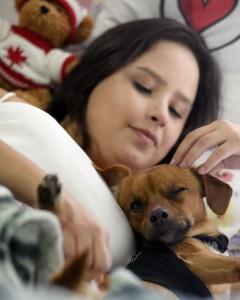 Animais: Imagem mostra menina com seu cãozinho deitados em uma cama