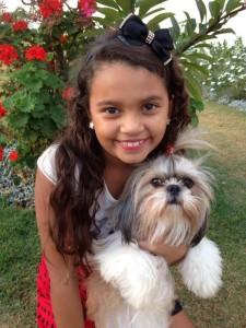 foto mostra garotinha com seu cãozinho.Adotar um pet